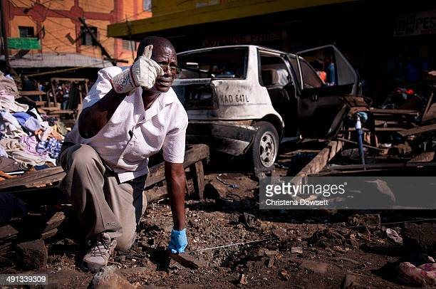 A member of the bomb squad measures the distance between two blast sites after twin improvised explosive devices went off in Gikomba market on May 16...