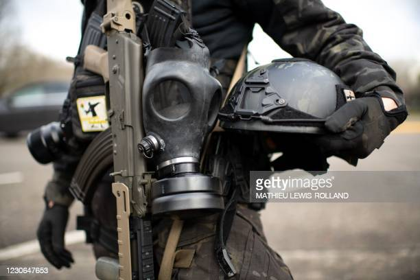 Member of the Boogaloo Boys stands armed with an assault rifle, gas mask and combat helmet outside of the Oregon State Capitol building in Salem on...