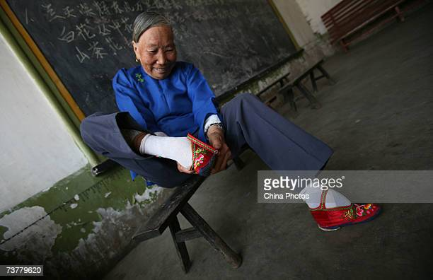 A member of the Bound Feet Women Dancing Team puts on her Three Cuns Golden Lotus shoe as she prepares for dancing practice at Liuyi Village on April...