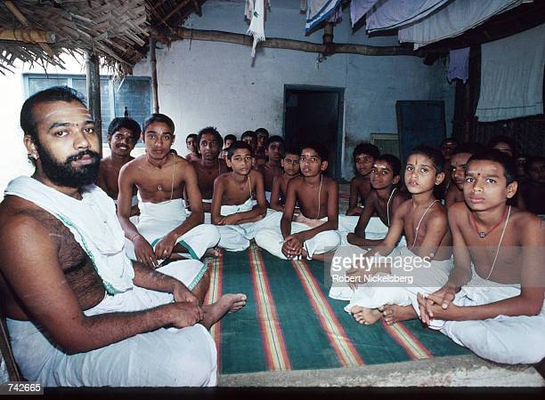 A member of the Brahmin caste sits with students October 28 1991 in India Of the five castes in Hinduism Brahmins occupy the highest level and are...
