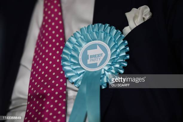 A member of the Brexit Party wears a rosette at a speaking event with party leader Nigel Farage and other candidates campaigning for the European...