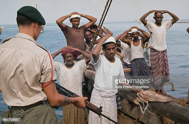 A member of the British armed forces Royal Marine commando conducts an armed search of a dhow and its crew for terrorist weapons off the coast of...