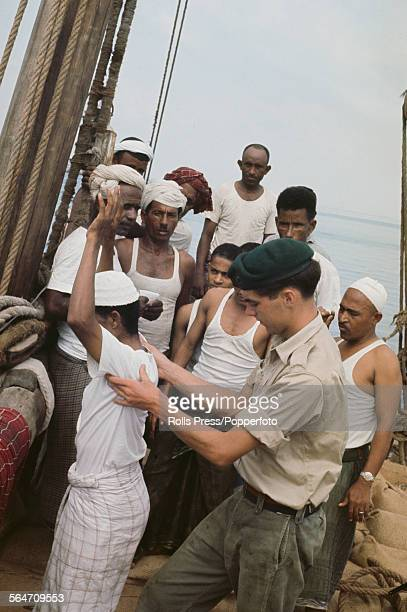A member of the British armed forces Royal Marine commando unit conducts a search of a crew member of a dhow for terrorist weapons off the coast of...