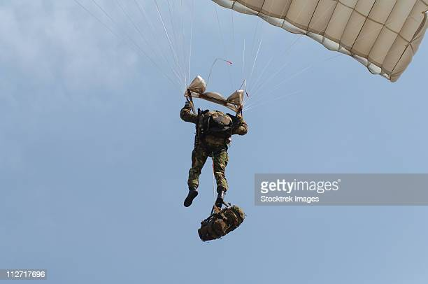 A member of the British Army Pathfinder Platoon prepares to land from a parachute jump.