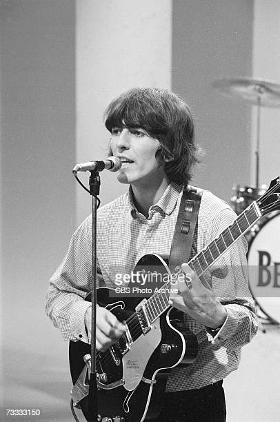 Member of the British rock band The Beatles George Harrison sings into a microphone as he plays his guitar at a rehearsal for the taping of a segment...