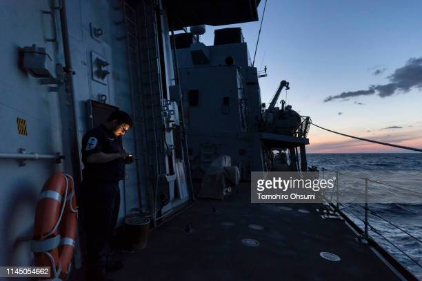 Member of the British Royal Navy uses a smartphone on the deck of the HMS Montrose frigate as it sails to a joint exercise with Japanese Maritime...