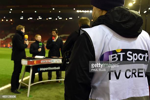 A member of the BT Sport broadcasting crew watches as pundits make their previews beside the pitch before kick off of the English Premier League...