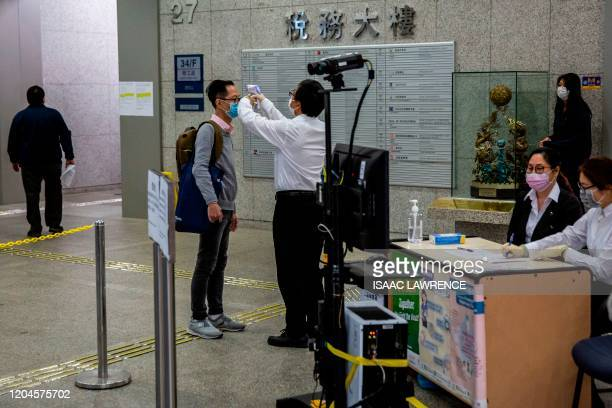A member of the building's security manually checks the temperature of a man at a temperature checkpoint as he enters a government office building in...