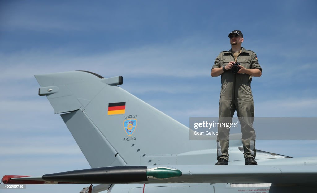 A member of the Bundeswehr stands on the wing of a jet fighter plane to take a picture at the ILA 2014 Berlin Air Show on May 21, 2014 in Schoenefeld, Germany. The ILA 2014 is open from May 20-25.