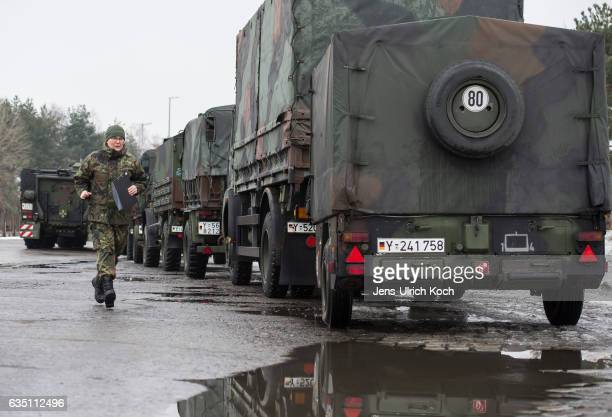 Member of the Bundeswehr the German armed forces passes military vehicles waiting to ship them and other equipment to Lithuania on January 31 2017 in...