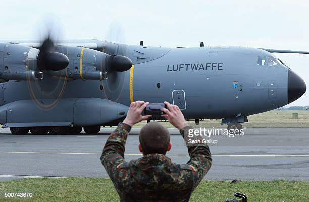 Member of the Bundeswehr, the German armed forces, snaps a photo of a Luftwaffe A-400M plane transporting 40 Bundeswehr members and their equipment...