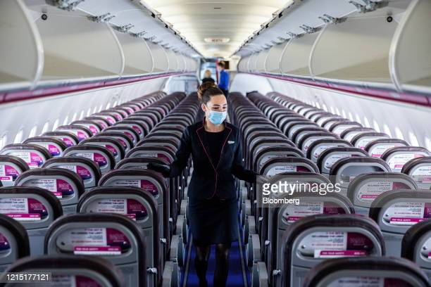 A member of the cabin crew wearing a protective face mask checks cabin seating ahead of the flight onboard a passenger aircraft operated by Wizz Air...