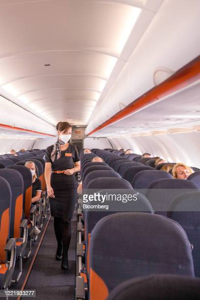 Member of the cabin crew, wearing a protective face mask, walks down the aisle of a passenger flight, operated by EasyJet Plc, on route from London...