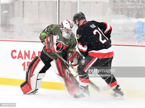 A member of the Canadian Armed Forces battles for a puck with Ottawa Senators alumni Dennis Vial during the 2017 Scotiabank NHL100 Classic Ottawa...