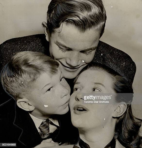 Member of the Canadian Army show; Lois Maxwell; being kissed by brother David; seven; as Keith looks on; stayed in London when the army show broke up...