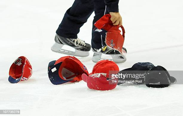 A member of the Capitals Ice Crew collects the hats tossed on the ice after Washington Capitals left wing Alexander Semin's hat trick in the second...