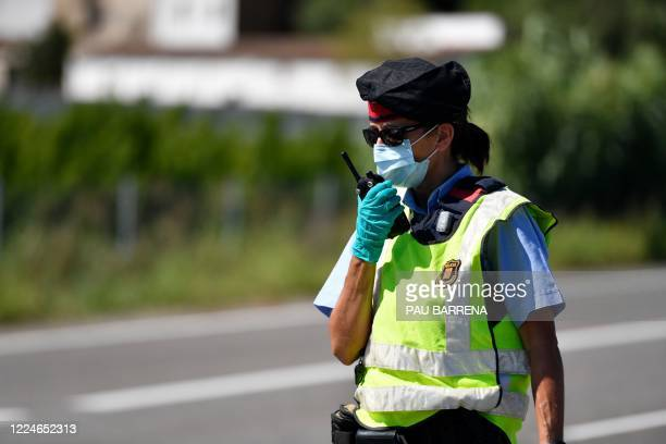 Member of the Catalan regional police force Mossos d'Esquadra controls a checkpoint on the Corbins highway near Lleida on July 4, 2020. - Spain's...
