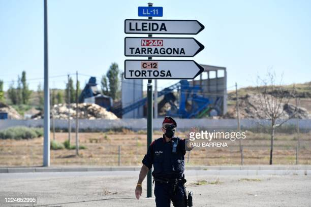 Member of the Catalan regional police force Mossos d'Esquadra controls a checkpoint on the road leading to Lleida on July 4, 2020. - Spain's...