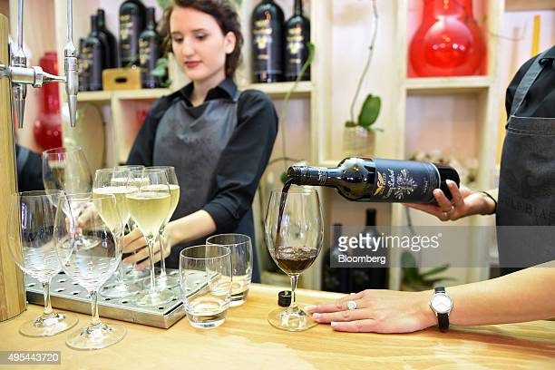 A member of the catering staff pours a glass of red wine at the Wolf Blass marquee during Melbourne Cup day at the Flemington racecourse in Melbourne...