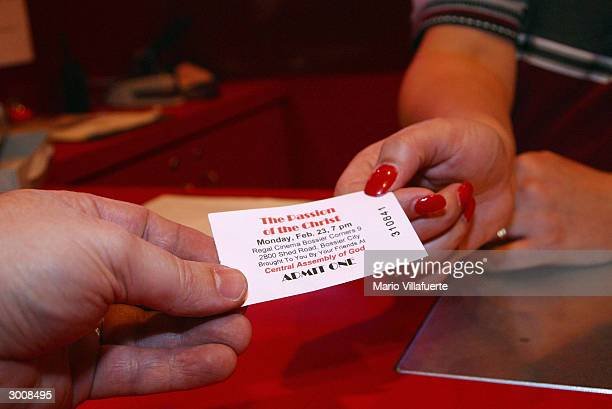 A member of the Central Assembly of God Church hands over a ticket for a prescreening of 'The Passion of the Christ' at a Regal Cinema movie theater...