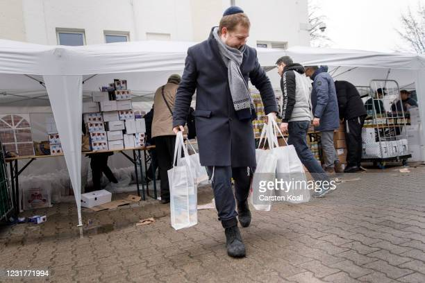 Member of the Chabad Berlin Jewish community carries packages for their needy co-members to a storeroom ahead of the Jewish holiday of Passover on...