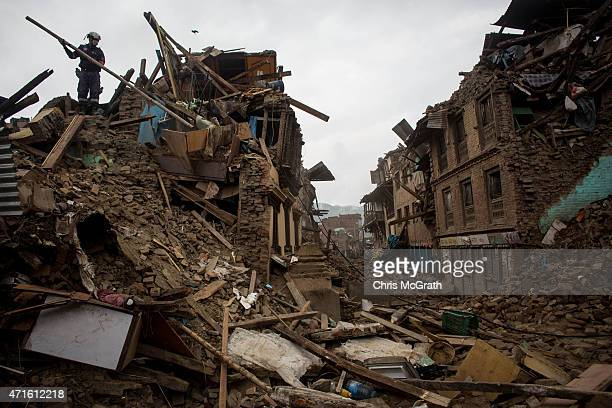 Member of the China search and rescue team pushes debris off the roof of a destroyed house in Shanku on April 30, 2015 in Kathmandu, Nepal. A major...