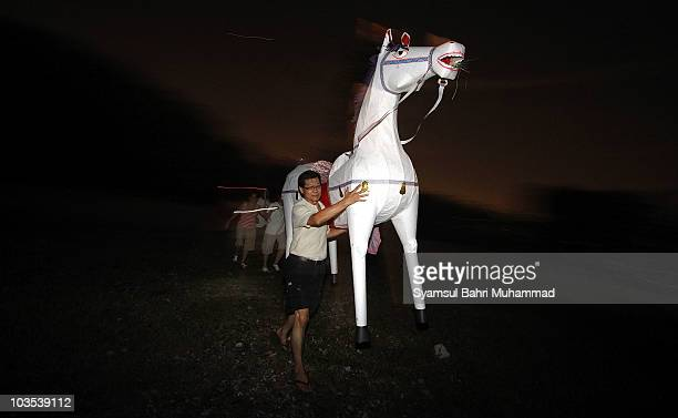 A member of the Chinese ethnic community carries a papermade horse during the Chinese Hungry Ghost Festival on August 22 2010 in Shah Alam Malaysia...