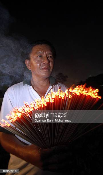 A member of the Chinese ethnic community holds joss sticks during the Chinese Hungry Ghost Festival on August 22 2010 in Shah Alam Malaysia The...
