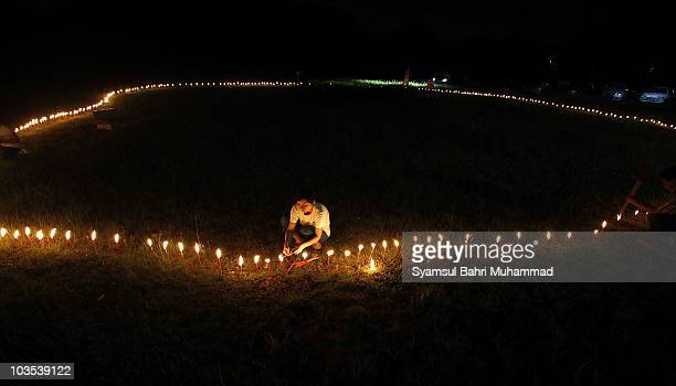 A member of the Chinese ethnic community lights candles during the Chinese Hungry Ghost Festival on August 22 2010 in Shah Alam Malaysia The Hungry...