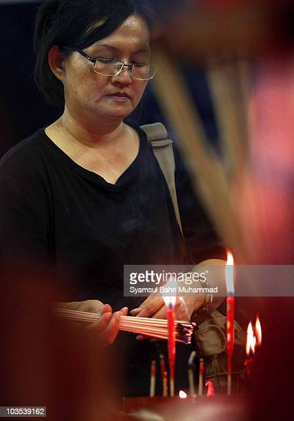 A member of the Chinese ethnic community lights joss sticks during the Chinese Hungry Ghost Festival on August 22 2010 in Shah Alam Malaysia The...
