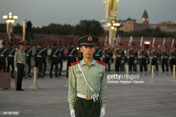 CONTENT] A member of the Chinese People's Armed Police Force stands guard during the daily lowering ceremony for the Chinese national flag at...