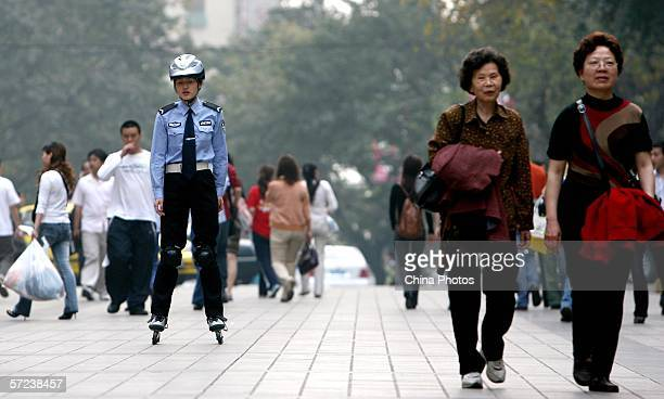 A member of the Chongqing Roller Skating Police Patrol Team performs her duty at the Jiefangbei Pedestrian Street April 3 2006 in Chongqing...
