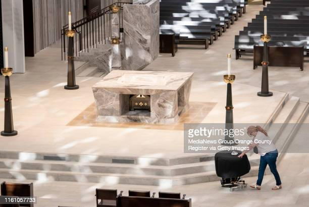 Member of the Christ Cathedral Brass moves her instrument past the marble altar at Christ Cathedral in Garden Grove on Monday, July 8, 2019. The...