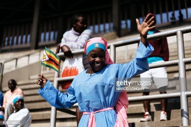 TOPSHOT A member of the Christian Church Jowani Masowe Vadzidzi Vajesu holds a Zimbabwean flag at the National Sport Stadium in Harare on November 24...
