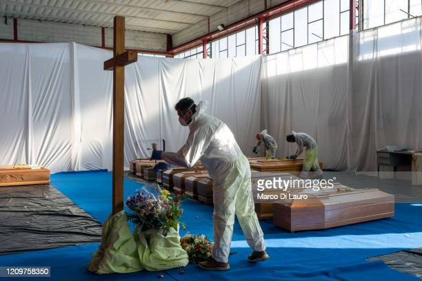 Member of the Civil Protection service collects a flower to rest on the coffin of a victim of COVID-19 in the hangar where 18 coffins wait to be...