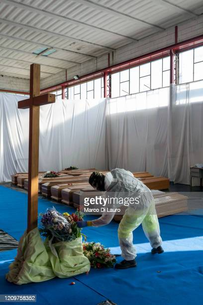 A member of the Civil Protection service collects a flower to rest on the coffin of a victim of COVID19 in the hangar where 18 coffins wait to be...