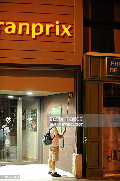 A member of the Clan du Néon turns off the neon light of a supermarket to save electricity late on July 9 2012 in Grenoble The Clan du neon is a...
