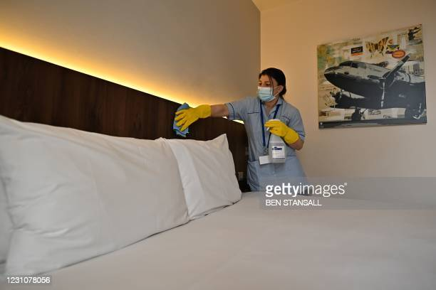 Member of the cleaning staff cleans surfaces as she prepares a room for a guest at the St Giles Hotel, near Heathrow Airport in west London, on...