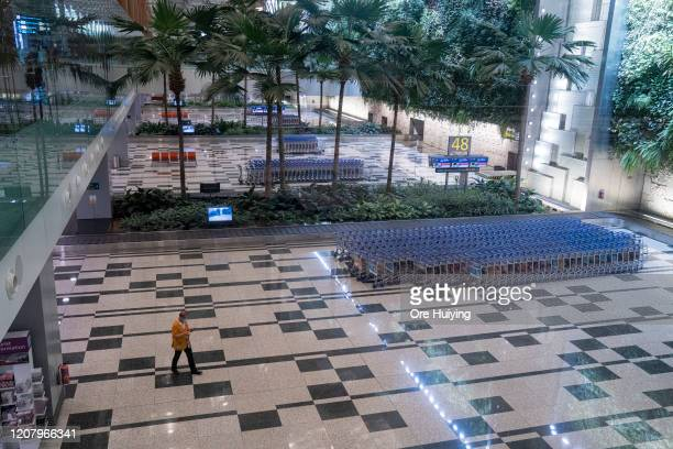 Member of the cleaning staff wears a face mask walking past an empty arrival hall at Changi Airport on March 22, 2020 in Singapore. To combat the...