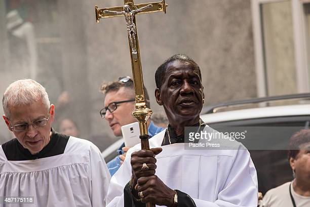 A member of the clergy at the Church of the Holly innocents carries a cross at the head of the traditional ceremony The congregation of the Church of...