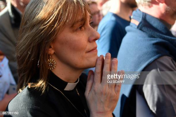 TOPSHOT A member of the clergy reacts during a vigil in Albert Square in Manchester northwest England on May 23 in solidarity with those killed and...