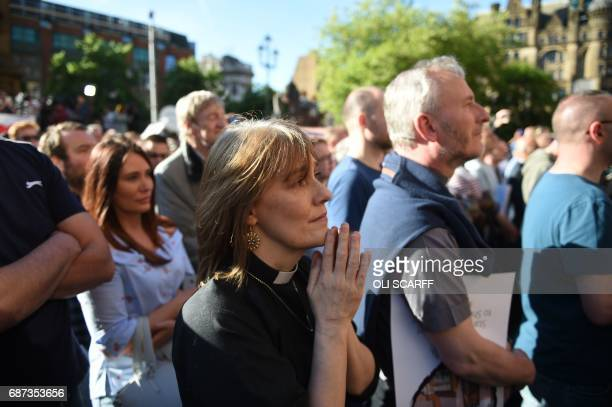 A member of the clergy reacts during a vigil in Albert Square in Manchester northwest England on May 23 in solidarity with those killed and injured...