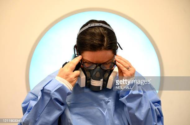 Member of the clinical staff adjusts her glasses as she dons personal protective equipment including a mask and gown at the Intensive Care unit at...