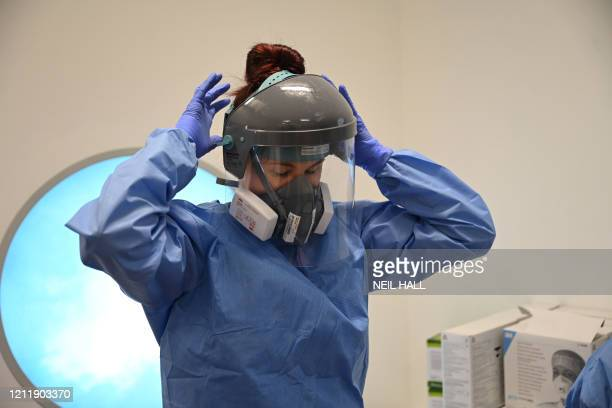 Member of the clinical staff dons personal protective equipment including a visor, mask, gown and gloves at the Intensive Care unit at Royal Papworth...