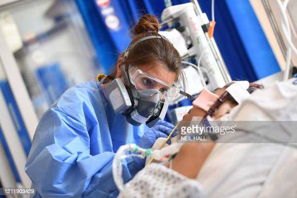 Member of the clinical staff wears personal protective equipment as she cares for a patient at the Intensive Care unit at Royal Papworth Hospital in...