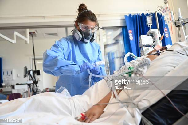 A member of the clinical staff wears personal protective equipment as she cares for a patient at the Intensive Care unit at Royal Papworth Hospital...