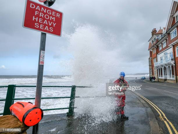 A member of the Coastguard stands on the seafront at Sandsend as big waves break onto the route during Stage 3 of the Tour de Yorkshire cycling race...