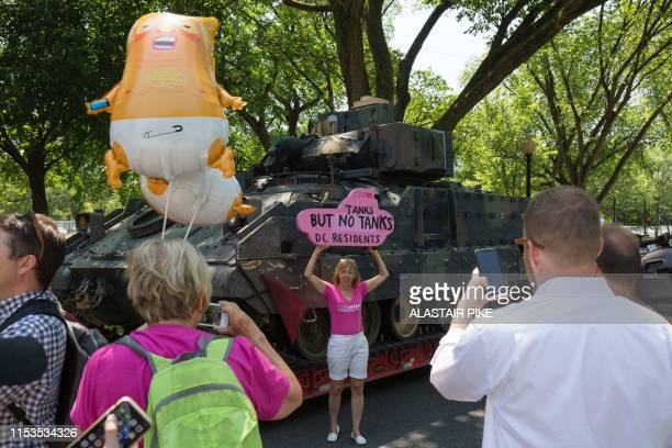 A member of the CodePink group poses in front a Bradley Fighting Vehicle ahead of the Salute to America Fourth of July event with US President Donald...