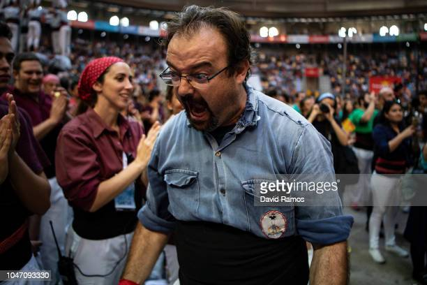 A member of the colla 'Xiquets del Serrallo' celebrates after building a human tower during the 27th Concurs de Castells competition on October 6...