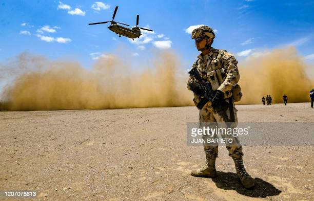 A member of the Colombian army stands by as a US army helicopter takes off during a joint exercise in the Tres Bocas area northern Colombia on the...
